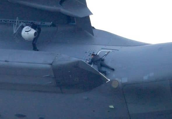 Close up of Tom Cruise strapped to the plane.